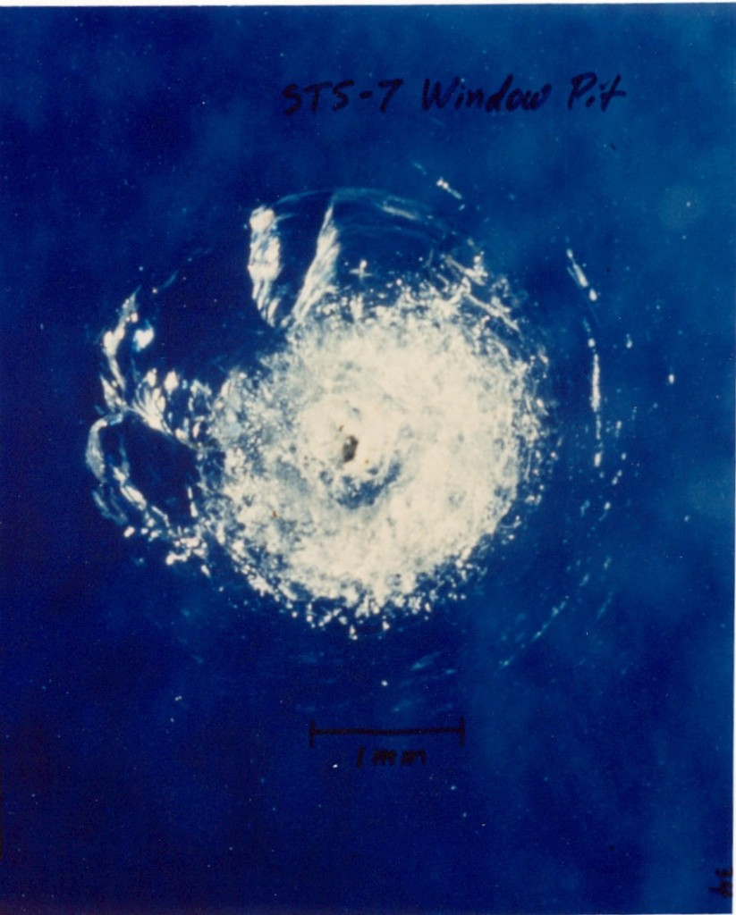 A window pit from an orbital debris impact from the STS-7 space shuttle mission.