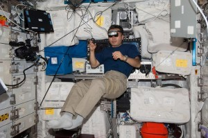 An ISS astronaut wearing a head-mounted display and holding a finger mouse in his hand performs the Reversible Figures experiment while free-floating.