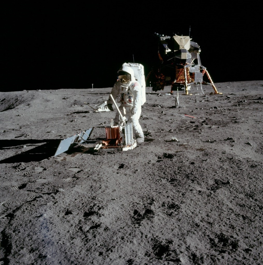 Buzz Aldrin deploys the solar panels of the Seismometer payload during the Apollo 11 mission to the moon. In the background is the spider-like Lunar Module.
